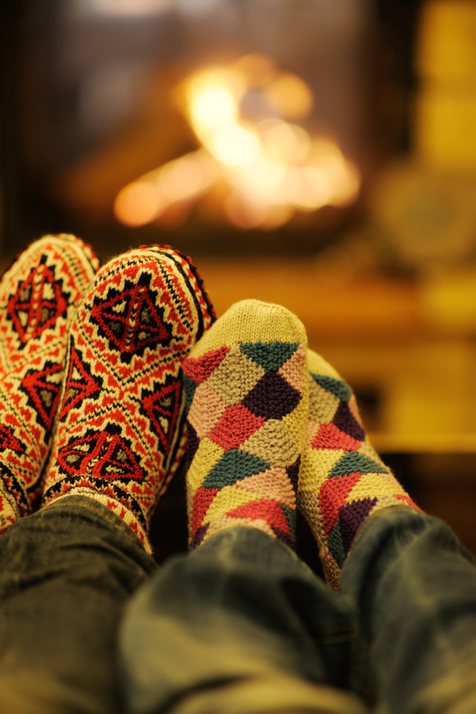 Couple with feet and socks together by the fire