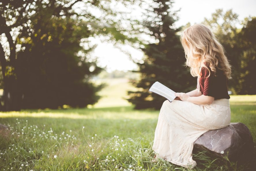 single girl sitting reading a book