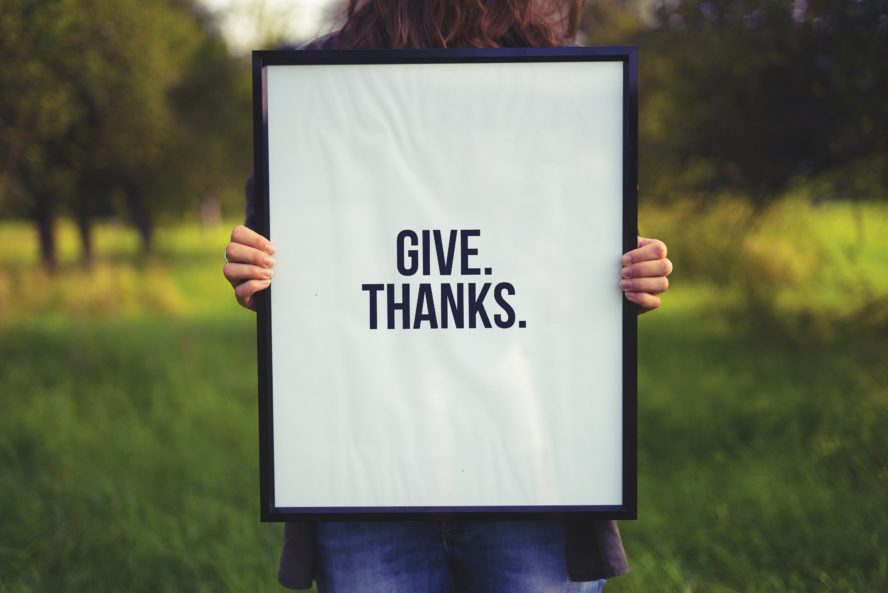 single holding a give thanks sign